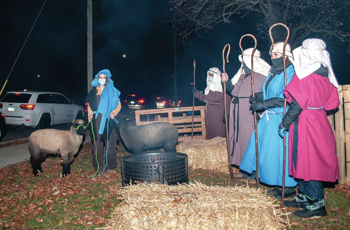 Lydia Pool - with sheep Bernice and Eliza - Linda Tribble, Brian Borgman, Rachel Borgman and Noah Borgman (left to right) stand at the shepherd station during the Centenary United Methodist Church's live Nativity drive-through Friday.