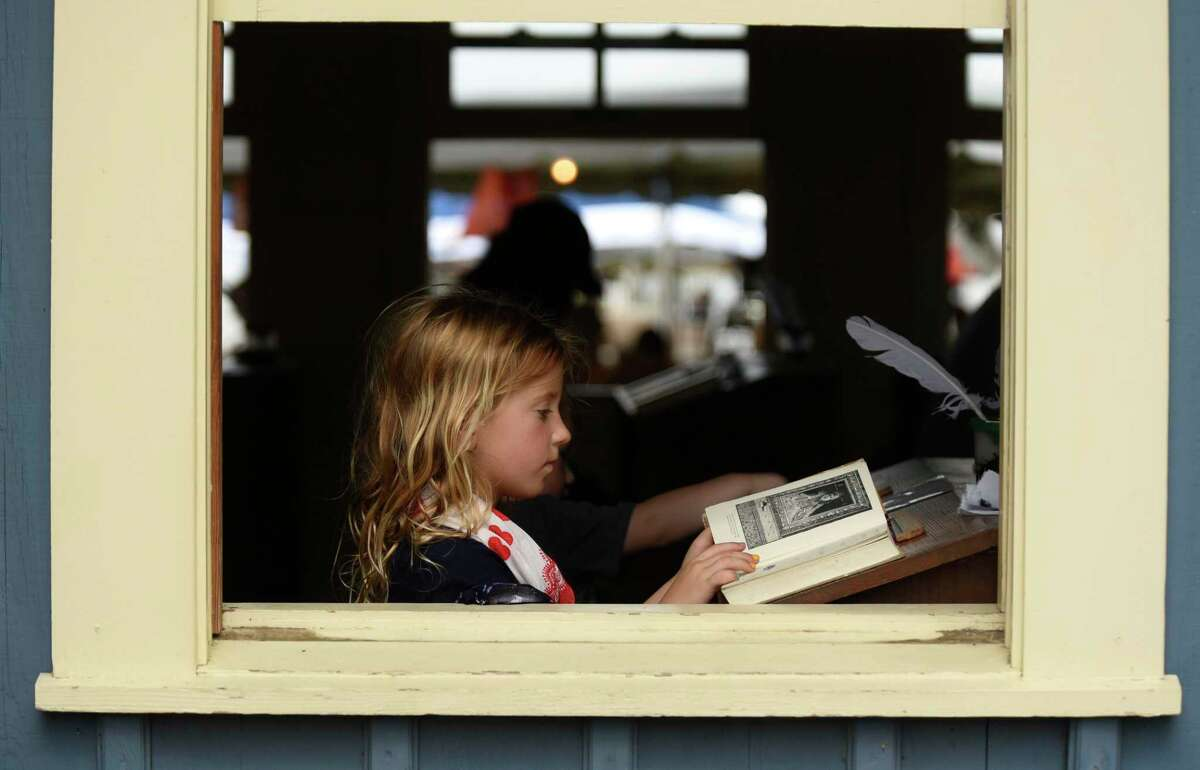 Willa Walter reads through an old book while sitting in a one-room school house during the Texas Folklife Festival on the grounds of the Institute of Texan Cultures.