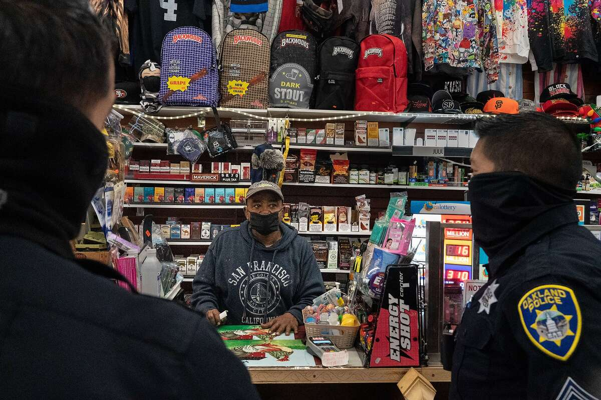 Oakland Officers Daniel Cornejo-Valdivia (left) and Bryant Ocampo chat with Fasil Lemma, owner of De Lauer's newsstand on Broadway.