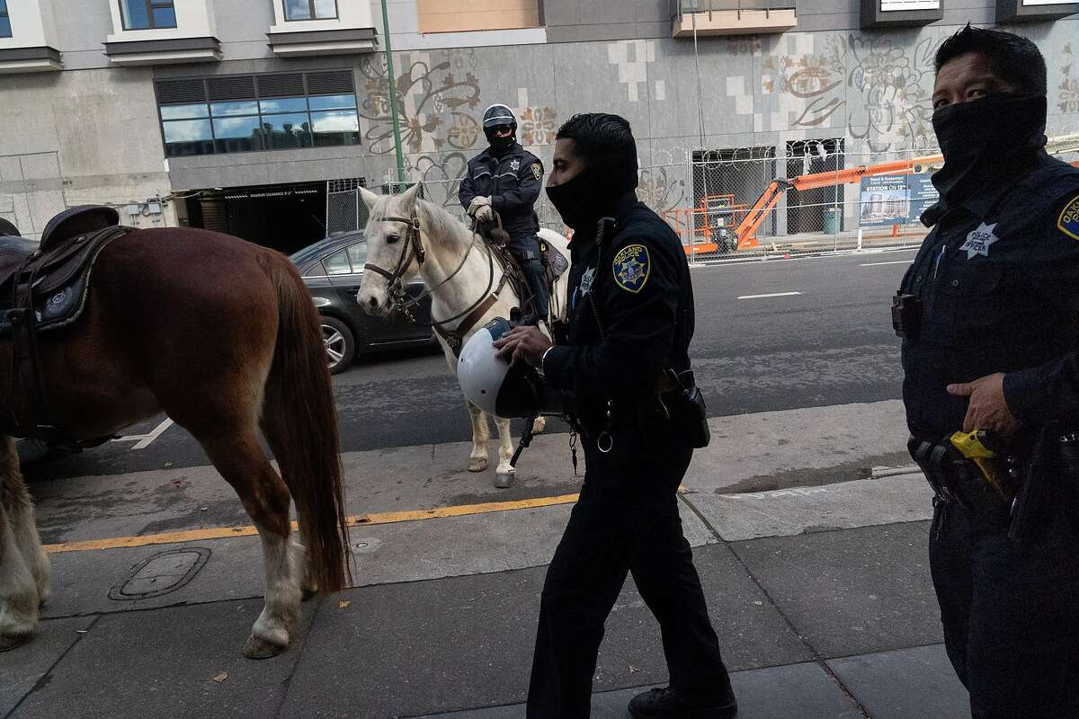 Oakland Officers Bryant Ocampo (right) and Daniel Cornejo-Valdivia visit with an officer on horseback patrolling downtown. The Police Department has eliminated details that put extra officers in areas with high rates of violent crime.