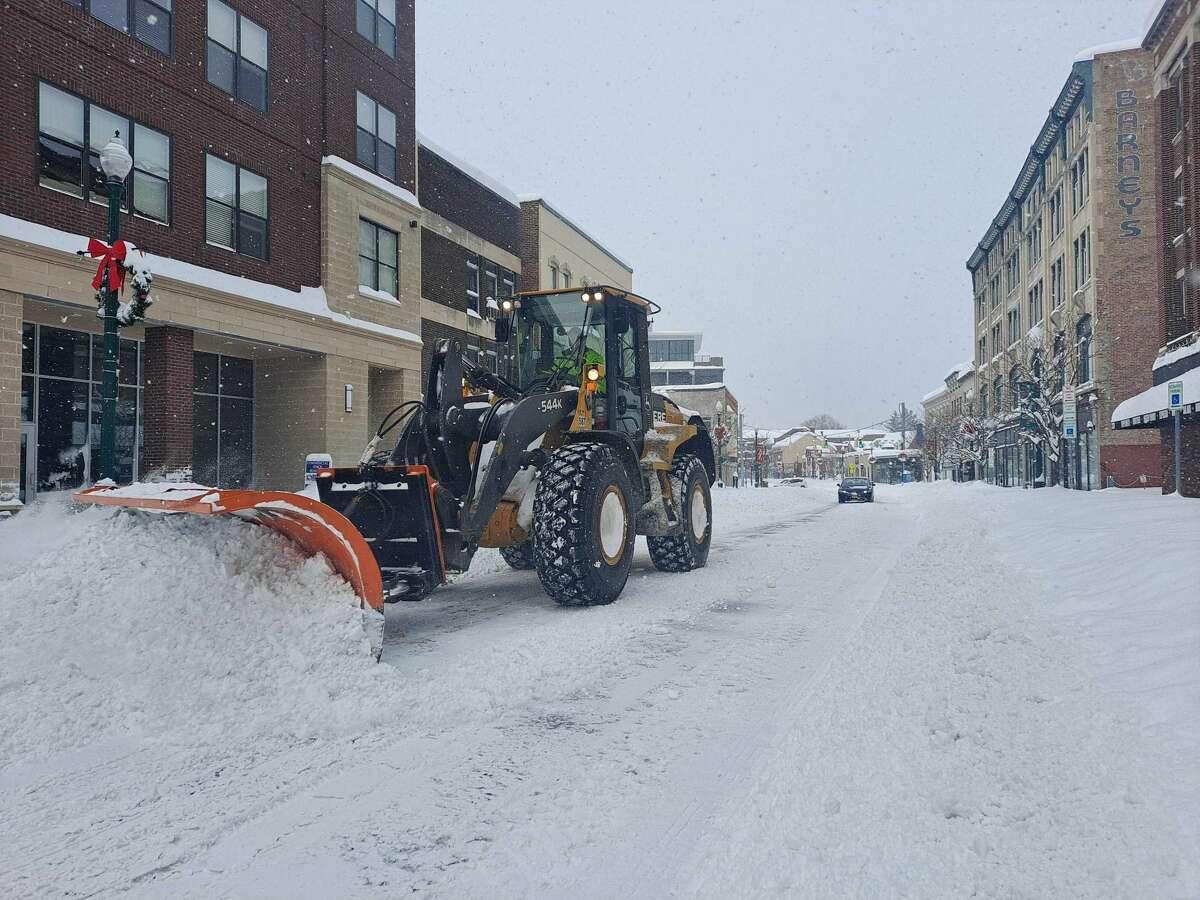 A plow follows an emergency vehicle along State Street toward Erie Boulevard in Schenectady on Thursday morning, Dec. 17, 2020.
