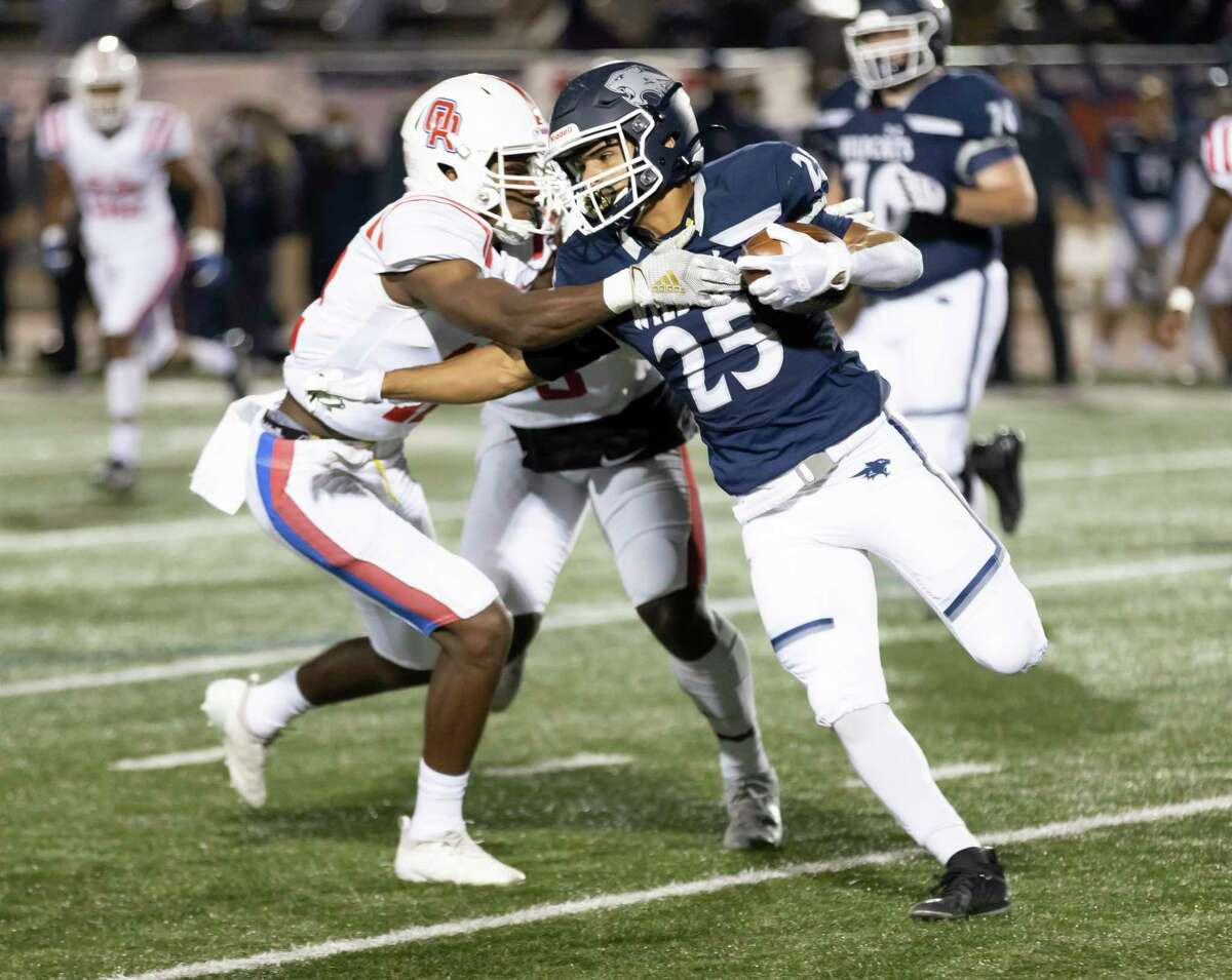 Tomball Memorial running back Richard Rodriguez (25) pushes passed Oak Ridge strong safety Jordan Holmes (22) during the second quarter of a Region II-6A area playoff game at Tomball ISD Stadium, Friday, Dec. 18, 2020, in Tomball.