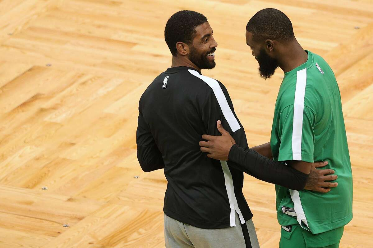 Ex-Celtic Kyrie Irving greets Jaylen Brown.
