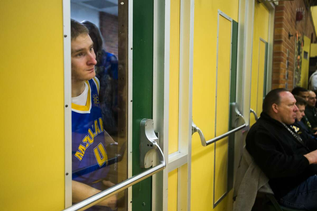 Midland High School student Tanner Bowerson peeks through a window into the gymnasium before playing in a unified basketball game against rivals from Dow Friday, Jan. 31, 2020 at H. H. Dow High School. (Katy Kildee/kkildee@mdn.net)