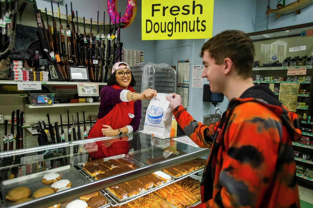Belinda Kuchek hands a bag of doughnuts to Jake Grames before he makes his purchase Monday, Feb. 10, 2020 at Ace Hardware & Sports in Midland. The store now sells doughnuts from Cops & Doughnuts, a popular Clare city bakery. (Katy Kildee/kkildee@mdn.net)