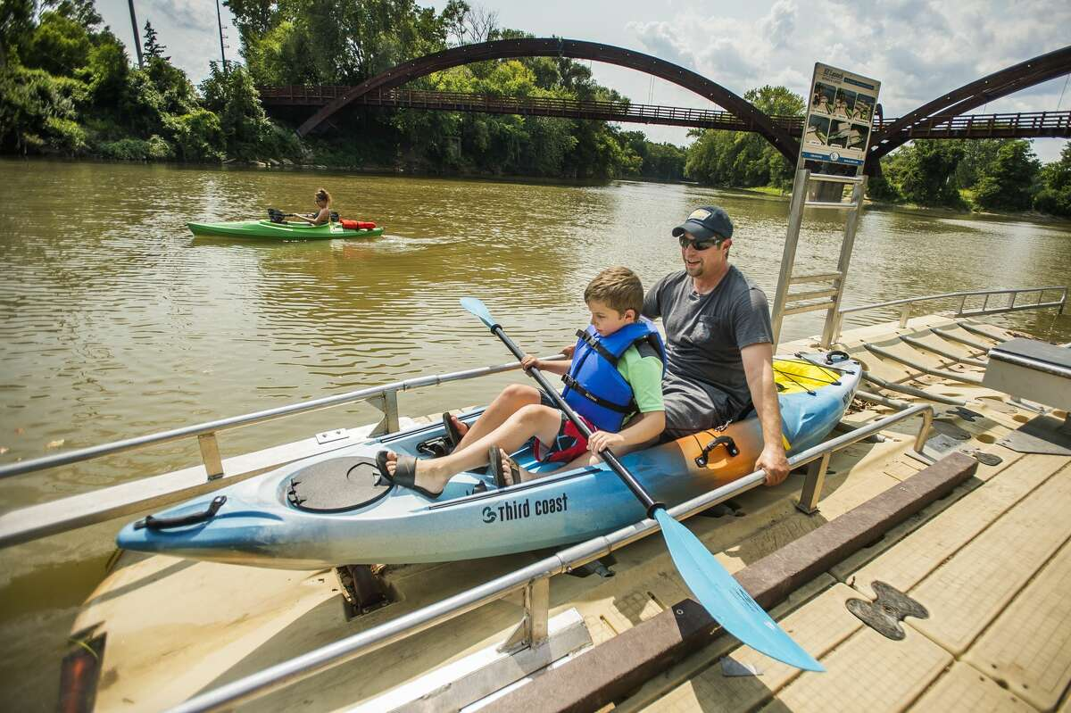 Mark Bunn, right, and his son Jackson, 8, center, push their kayak towards the water of the Tittabawassee River from the canoe/kayak launch as Hailey Bunn, 16, left, paddles nearby Monday, Aug. 24, 2020 near the Tridge in Midland. (Katy Kildee/kkildee@mdn.net)