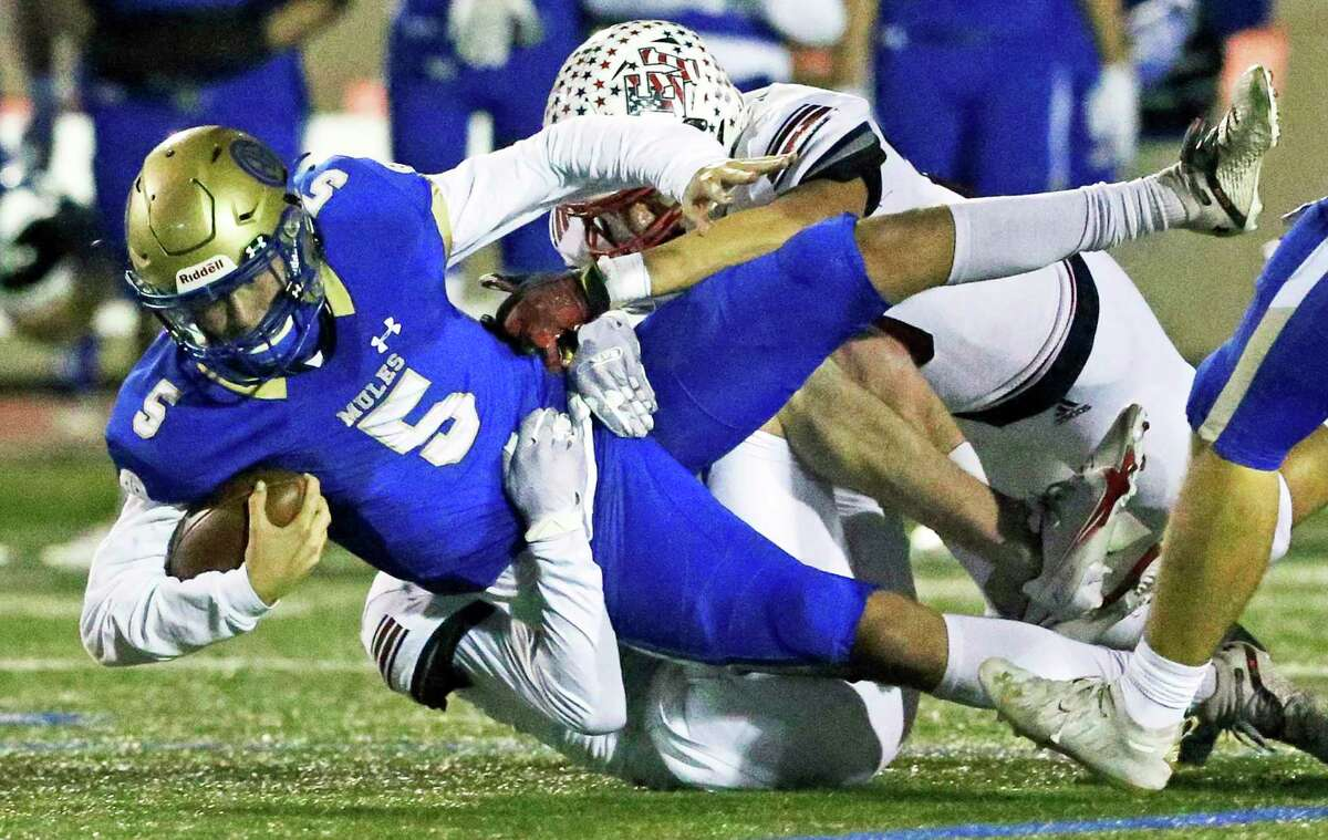 Mules quarterback James Sobey is yanked down by a pair of Patriot defenders as Alamo Heights plays Georgetown East View at Comalander Stadium in high school football playoffs Stadium on Dec. 18, 2020.