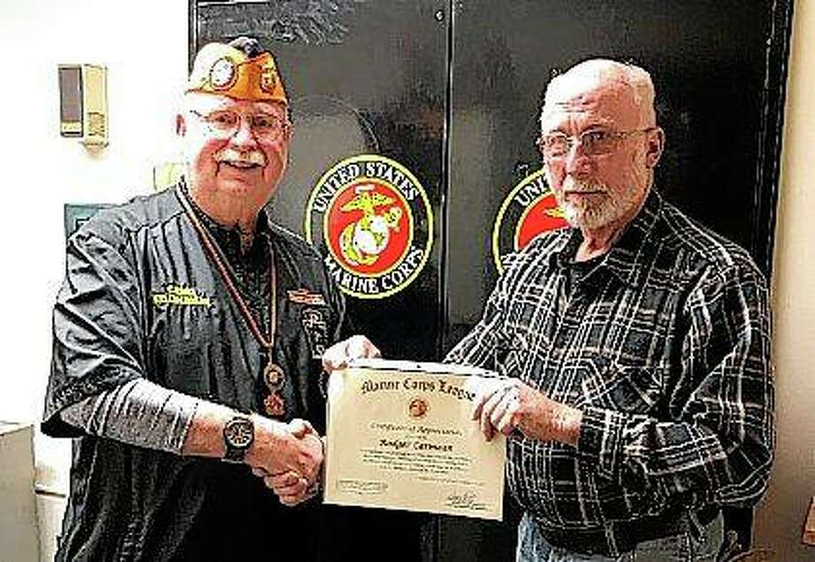 C.O. Smith (left) of the Jacksonville Marine Corps League presents a certificate of appreciation to Rodger Carmean for his help in moving heavy items from the V.F.W. to the American Legion.