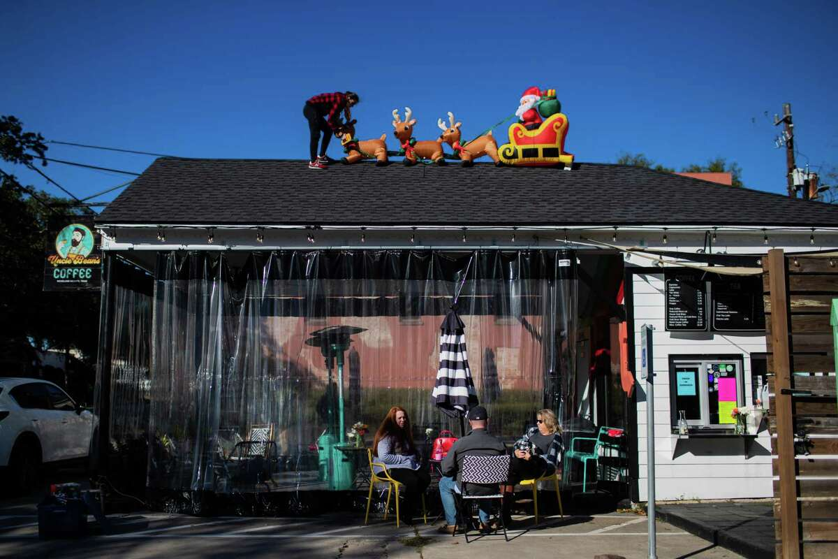 Cora Hendrix, sister of the owner of Uncle Bean's Coffee, installs Christmas decorations on the roof of the coffee shop in the Heights on Nov. 30.