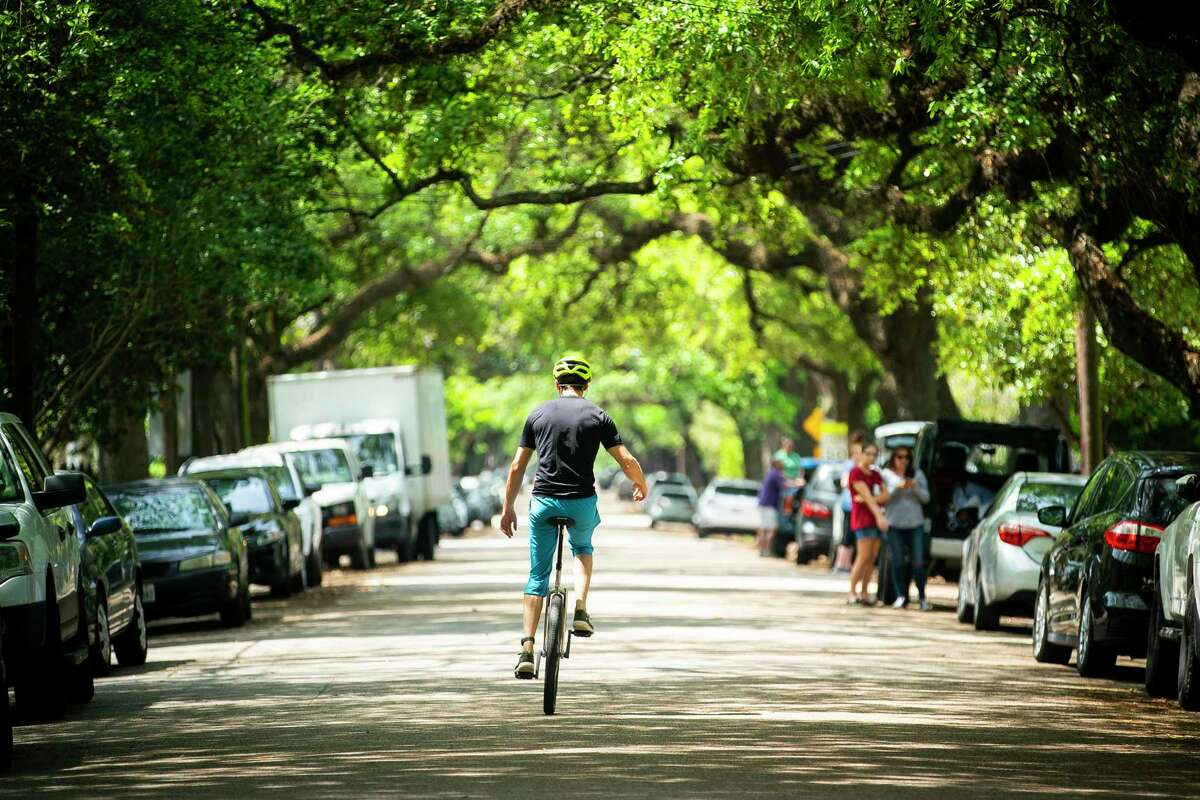 A man rides a unicycle down Bayland Avenue before a parade of teachers from Travis Elementary School and other local school drive through the neighborhood near the school, Friday, March 27, 2020, in the Heights area of Houston.