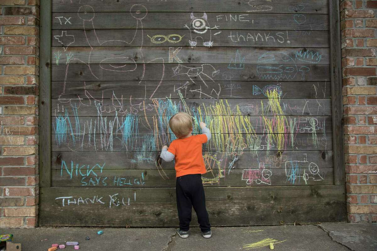 Nicholas Krysiek, 2, draws on a fence filled with inspirational thank you and stay safe messages with chalk in the Heights on Tuesday, May 5, 2020 in Houston.