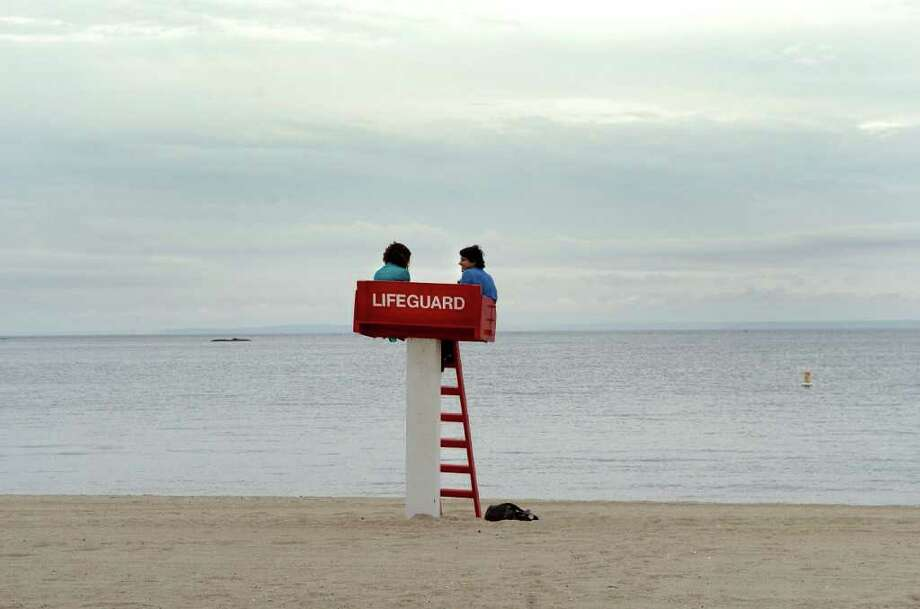 Shameka Frederick and Alex Gutierrez sit on the lifeguard chair at Cunmmings Beach waiting for Hurricane Earl in Stamford, Conn. on Friday September 3, 2010. Photo: Dru Nadler / Stamford Advocate Freelance