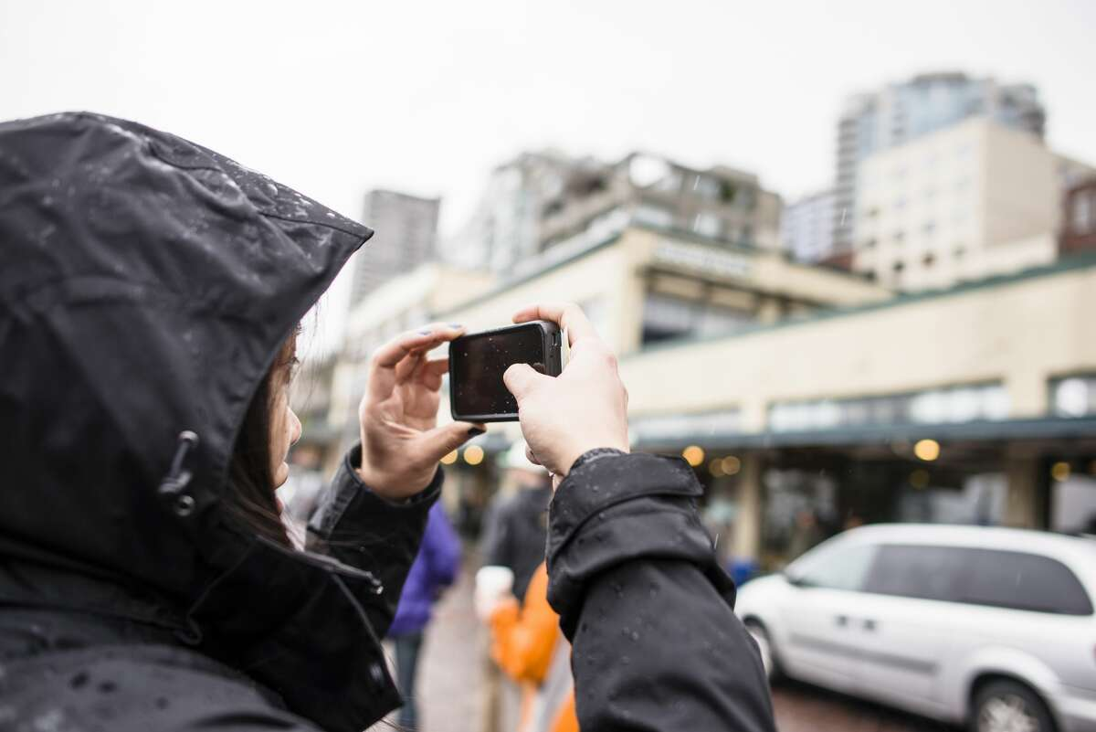 Female tourist photographing on smartphone at Pike Place market in Seattle, Wash.