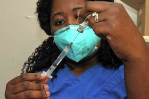 Nurse Daphney Hippolyte fills a syringe with a dose of the Pfizer COVID-19 at Stamford Hospital, in Stamford, Conn. Dec. 17, 2020.
