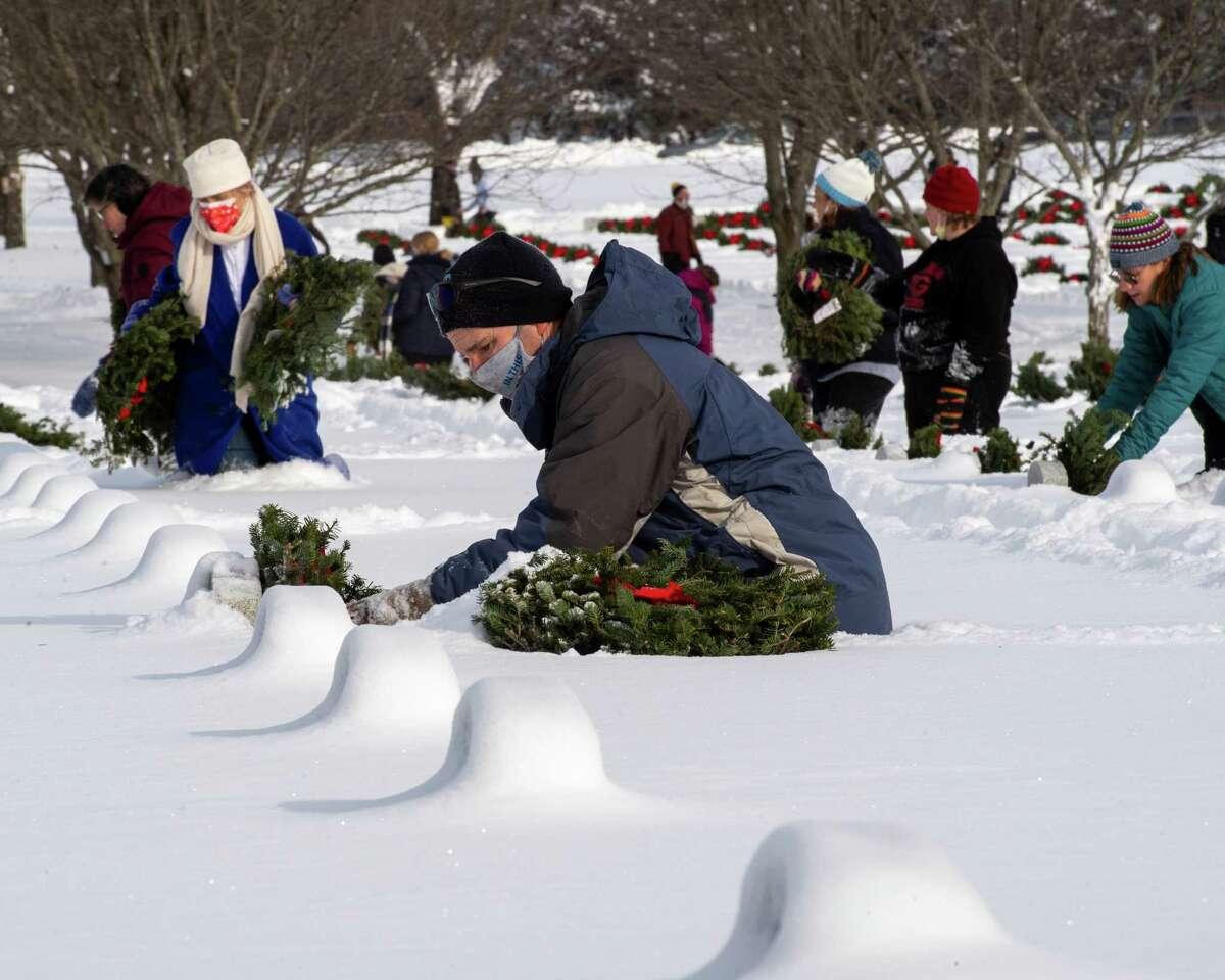 Tom Averill lays a wreath on a grave during national Wreaths Across America Day at the Gerald B.H. Solomon Saratoga National Cemetery in Schuylerville, NY, on Saturday, Dec. 19, 2020 (Jim Franco/special to the Times Union.)