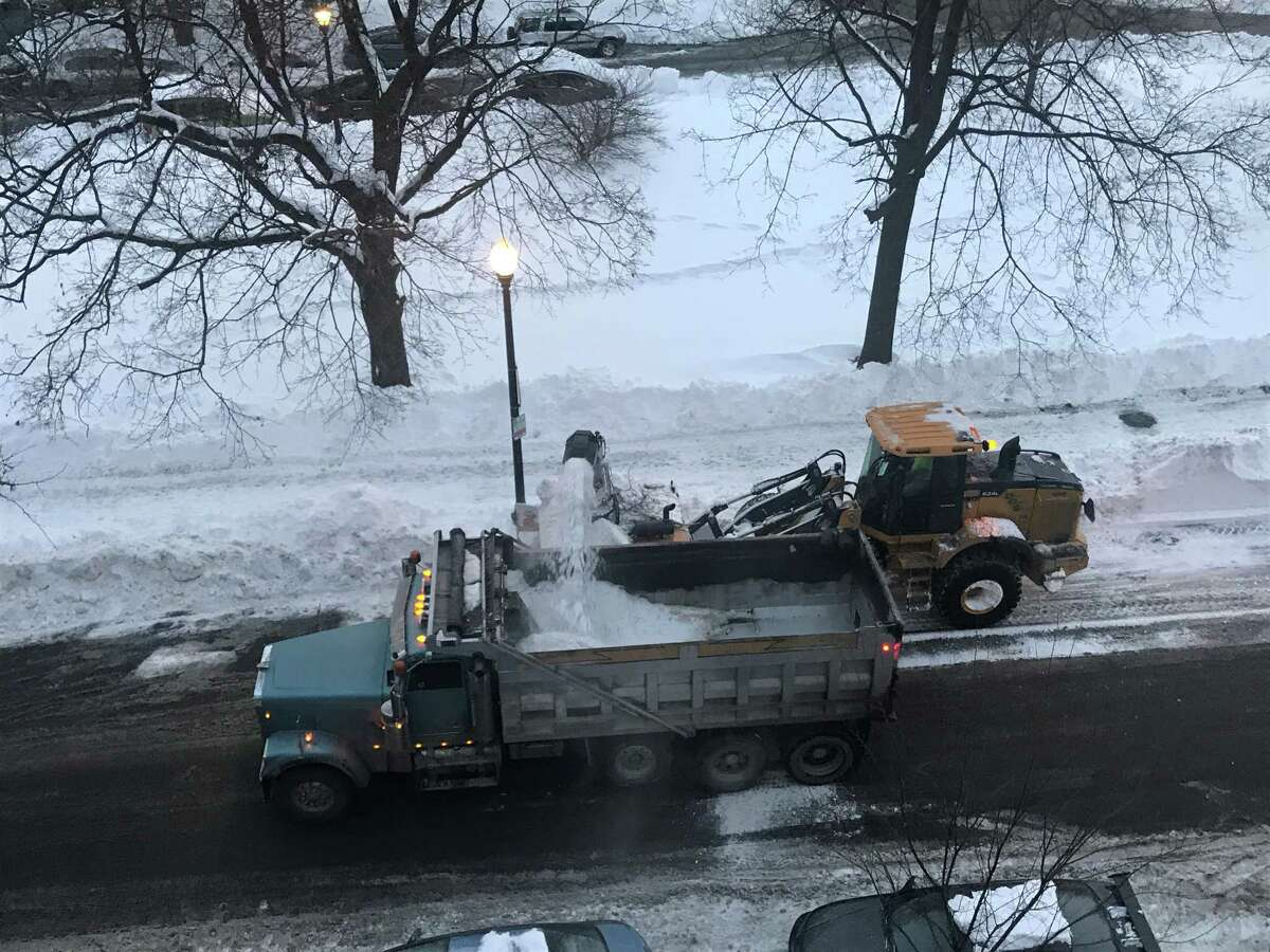 An Albany crew rolls down State Street by Washington Park Saturday, Dec. 20, 2020 blowing show to clean the even side of the street during the second day of the city's snow emergency.