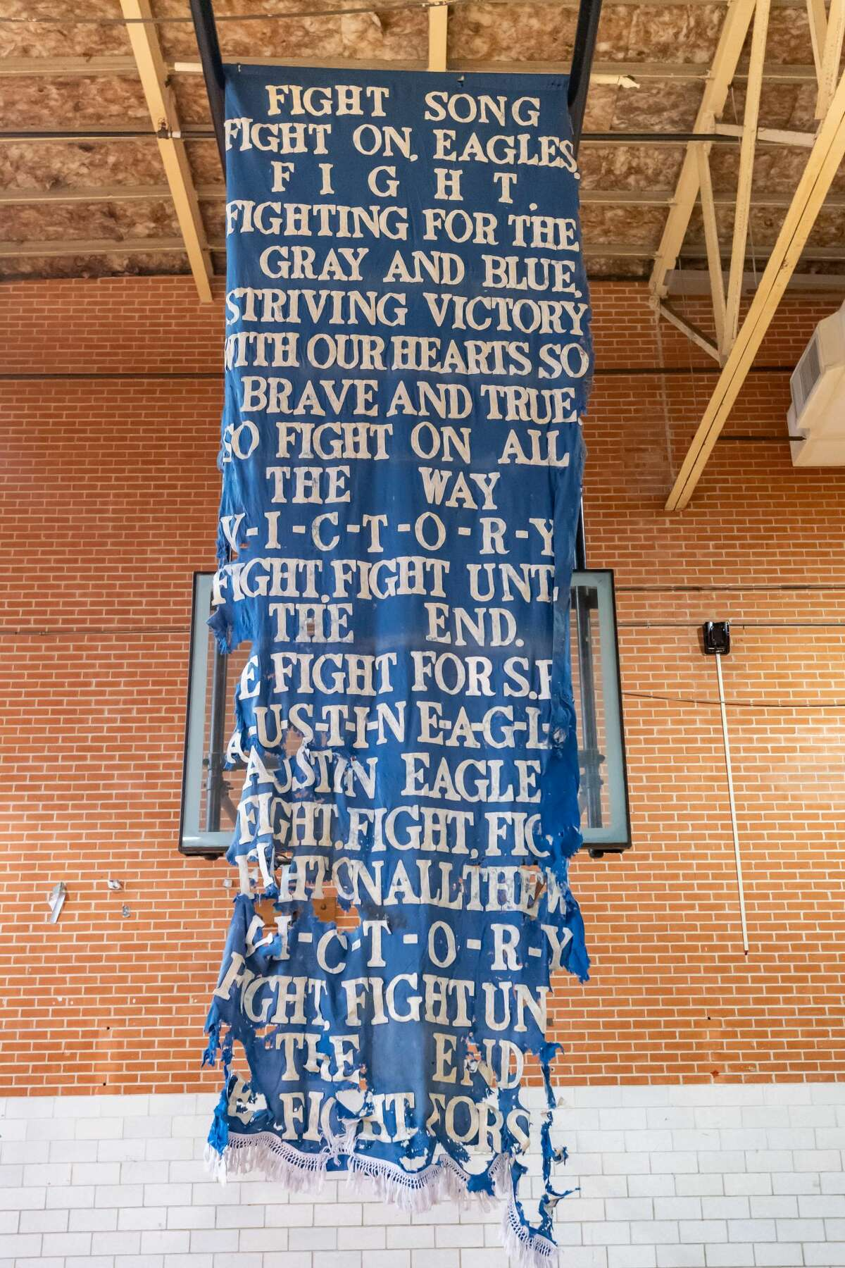 A tattered banner with the SFA fight song hands in the gym on the west side of the school. The former Stephen F Austin high school had been a central part of the Port Acres community but has been closed for several years and is scheduled to be demolished in the near future. Former students were invited to visit the school for the last time to relive their memories. Photo made on December 19, 2020. Fran Ruchalski/The Enterprise