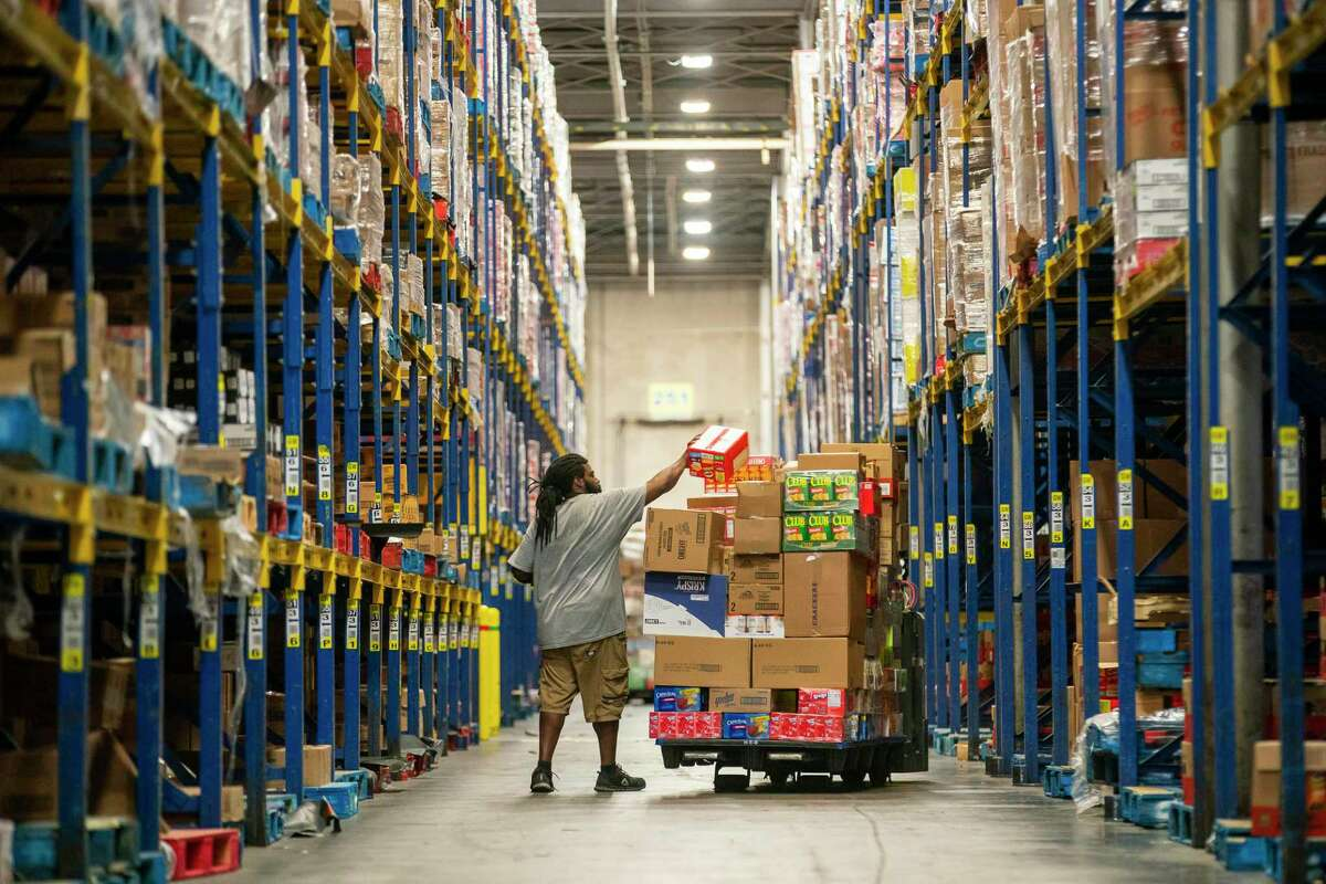 Essential workers inside HEB's Houston warehouse and distribution center, move product through to meet the increased demand from the retail stores.