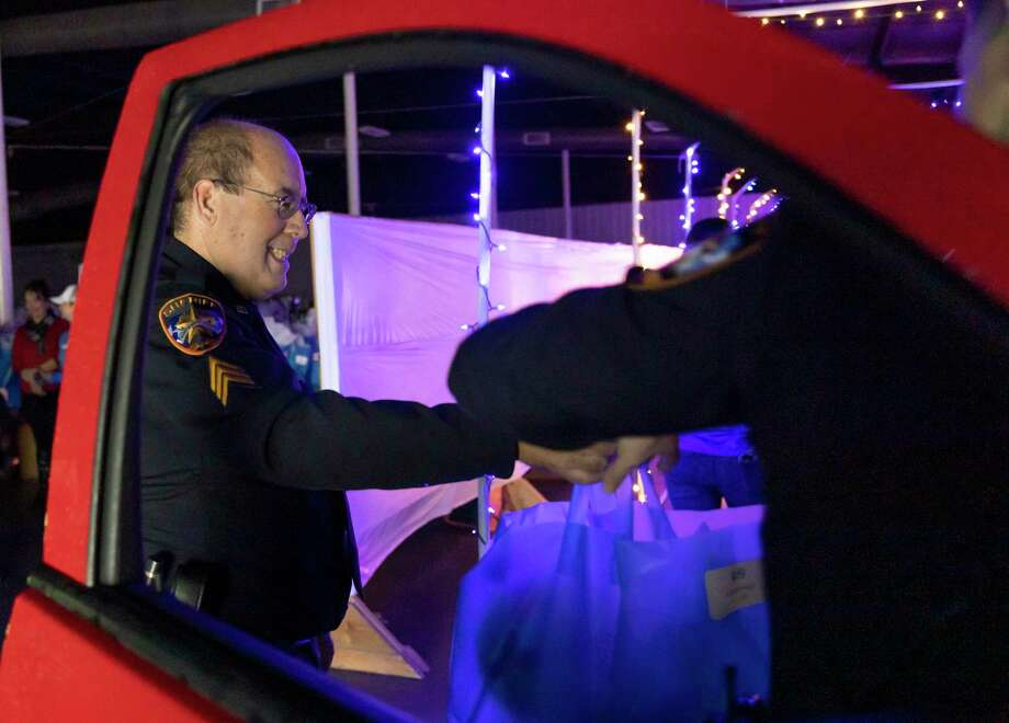 Sgt. David Miller with the Montgomery County Sheriff's Office hands a bagged gift to a family during the Operation Blue Elf event at the Montgomery County Fairgrounds, Saturday, Dec. 19, 2020, in Conroe. The MCSO and partners were able to handout hundreds of gifts through a drive-thru style events. Photo: Gustavo Huerta, Houston Chronicle / Staff Photographer / 2020 © Houston Chronicle
