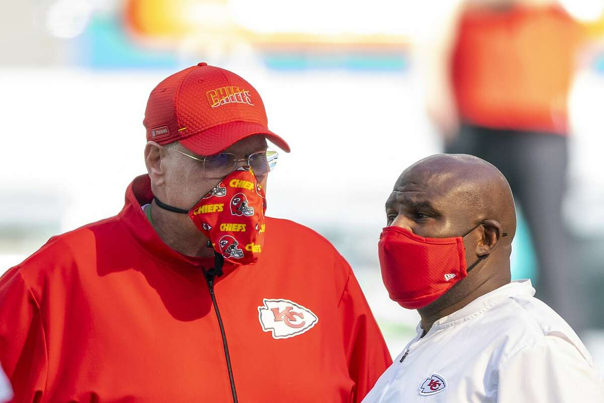 From left, Kansas City Chiefs head coach Andy Reid and Kansas City Chiefs offensive coordinator Eric Bieniemy wear masks as they talk on the field before the Chiefs take on the Miami Dolphins during an NFL football game, Sunday, Dec. 13, 2020, in Miami Gardens, Fla.
