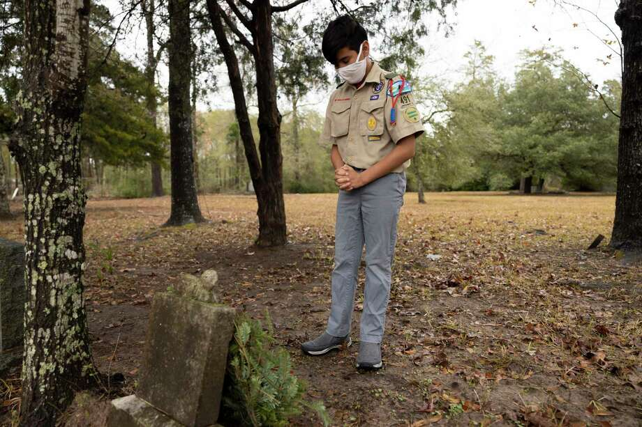 Johnathan Serrano, with Boy Scouts Troop 491, partakes in a moment of silence after placing a wreath at a veterans gravesite during the 2nd annual Wreaths Across America event held at Oakwood Cemetery, Saturday, Dec. 19, 2020, in Conroe. Wreaths are placed at the graves of veterans to honor their service during the holiday season. Photo: Gustavo Huerta, Houston Chronicle / Staff Photographer / 2020 © Houston Chronicle