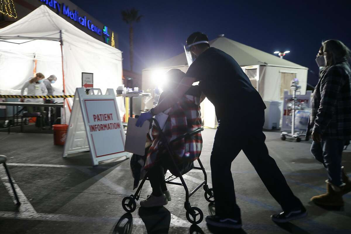 A California National Guard medic pushes an incoming patient past triage tents set up outside Providence St. Mary Medical Center amid a surge in COVID-19 patients in Southern California on December 18, 2020 in Apple Valley.