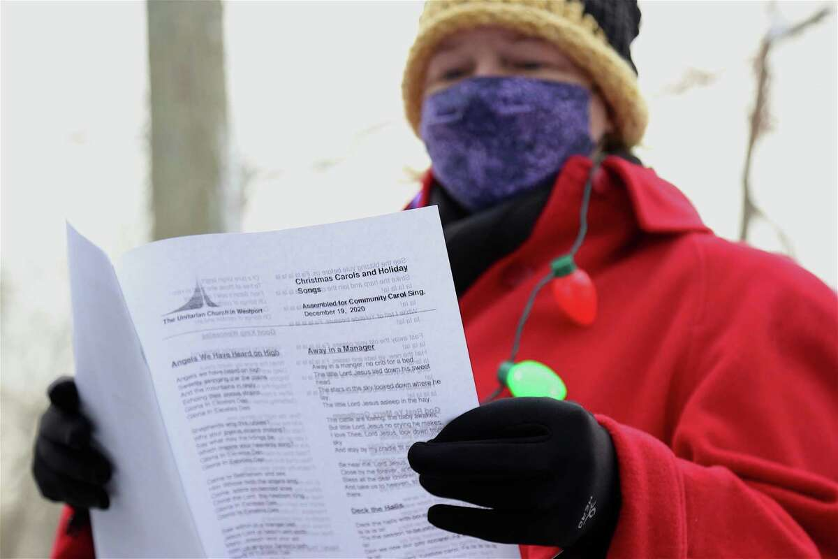 Amy Arnone, of Trumbull, consults the song sheet at the caroling get-together at The Unitarian Church in Westport on Saturday, Dec. 19, 2020. More than 50 participants-all in masks-assembled in a large circle in the big parking lot off Lyons Plains Road. Spurred on by a song sheet Cliff created featuring a range of holiday hits-as well as marvelous French horn accompaniment by Pawelek-people happily sang out with the sounds of the season.