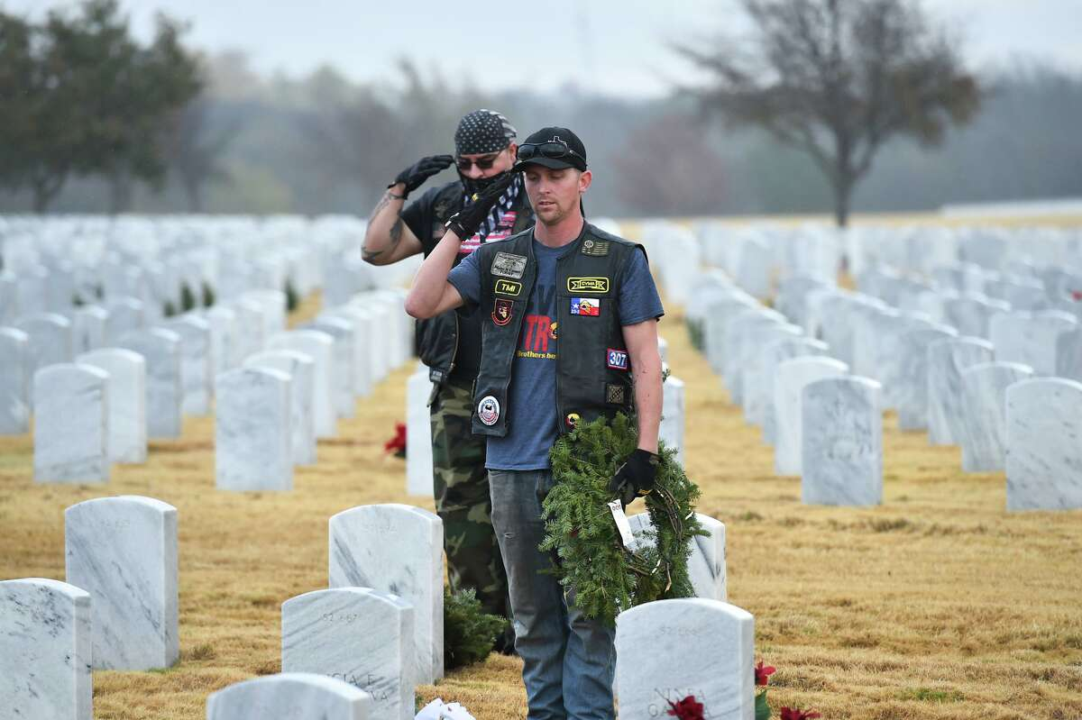 Daniel Lyautey (foreground) and Steven Noble salute after placing wreaths during the Wreaths Across America effort. Volunteers put wreaths on the headstones at Fort Sam Houston National Cemetery on Saturday morning. Last year, the group placed 56, 322 wreaths .