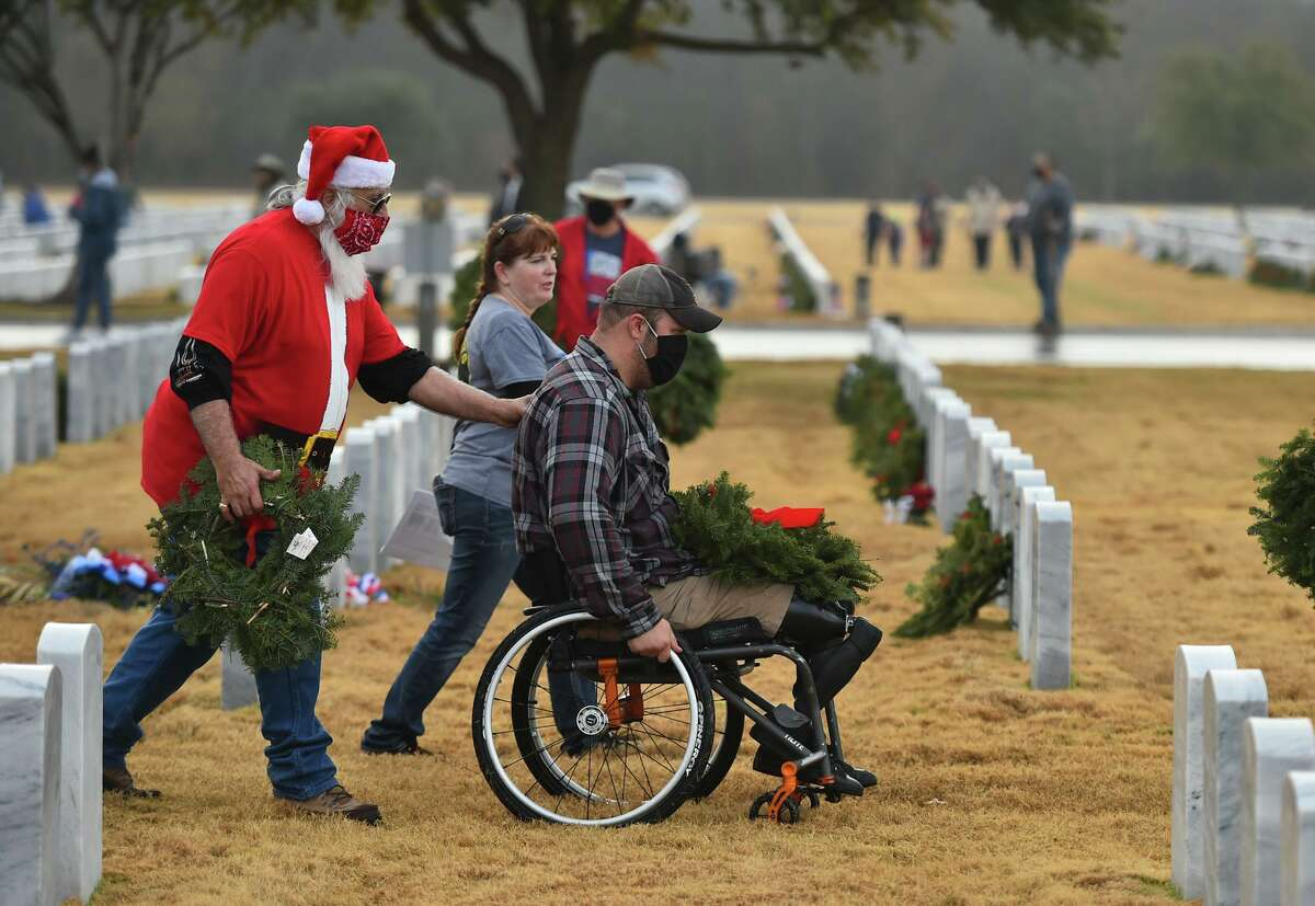 Iraq Marine veteran Neil Frustaglio is assisted by Al Salazar and Diane Hotaling during the annual Wreaths Across America event at Fort Sam Houston National Cemetery on Saturday morning.