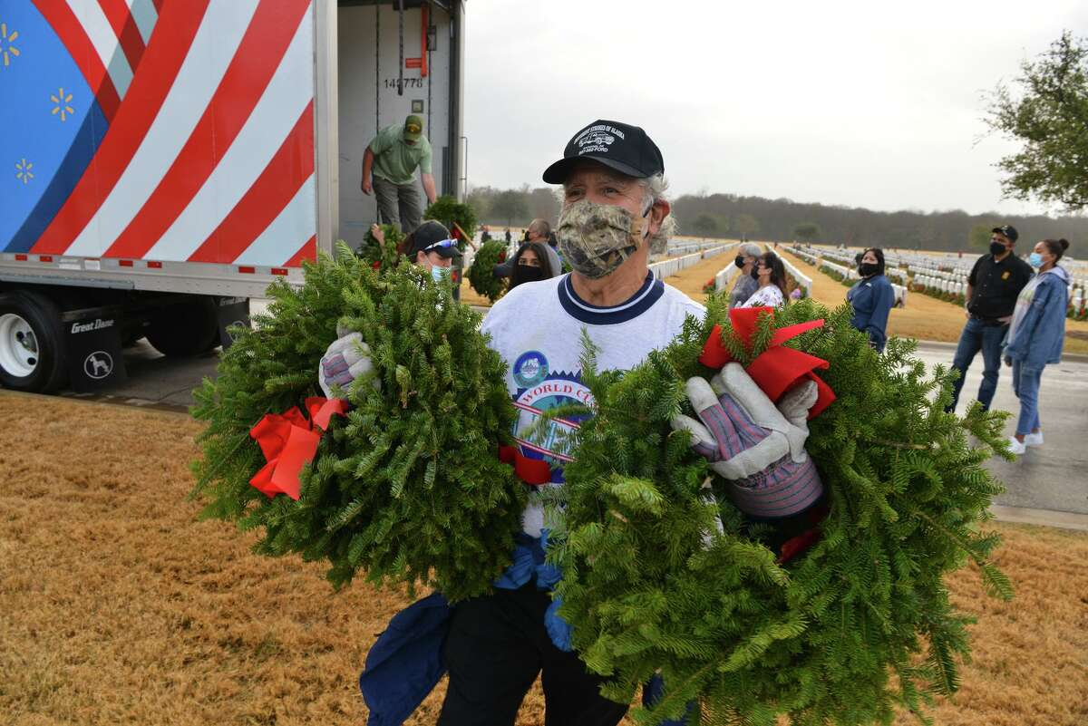 Ray Martinez carries wreaths during Wreaths Across America as volunteers put wreaths on the headstones at Fort Sam Houston National Cemetery Saturday morning. Last year the group placed 56, 322 wreaths on the headstones of those buried at Fort Sam.