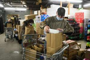 Rob Meyette of Sanford loads groceries into a bag before they are donated to Sanford flood victims through a partnership between The Food Center in Sanford and the Elks Club Friday, Dec. 18, 2020. (Katy Kildee/kkildee@mdn.net)