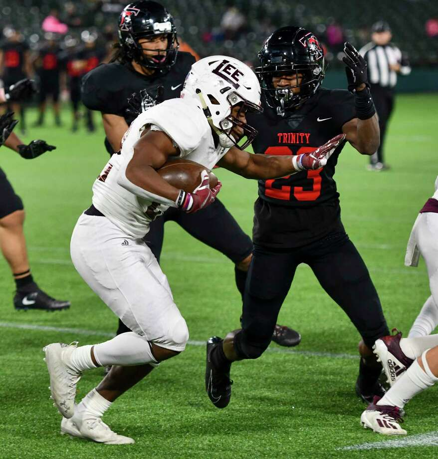 Lee's Makhilyn Young attempts to make his way past Trinity's Damarion Dean (23) on Saturday, Dec. 19, 2020 at Globe Life Park in Arlington. Jacy Lewis/Reporter-Telegram Photo: Jacy Lewis/Reporter-Telegram