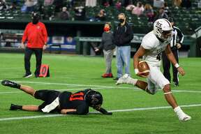Lee's Mikey Serrano (4) runs in for a touchdown as Trinity's Sateki Wolfgramm (11) trips behind him Saturday, Dec. 19, 2020 at Globe Life Park in Arlington. Jacy Lewis/Reporter-Telegram