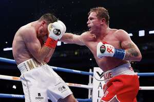 Canelo Alvarez punches Callum Smith during their super middleweight title bout at the Alamodome on Dec. 19, 2020 at the Alamodome.