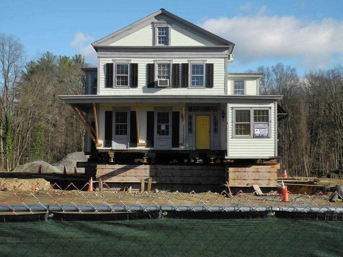 The development 200 Sharp Hill Square was created around preserving the historic Raymond-Morehouse House, which was the former Sheridan Interiors furniture store. On Dec. 10, the building is ready to be moved on the building site. Two buildings combining residential and retail will be built at the Danbury Road property.