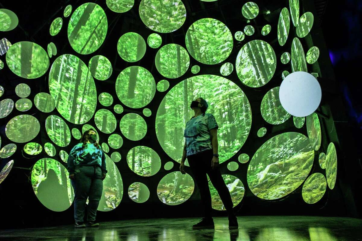 Seismique's guides Felicia Berrios, left, 28, and Sara Ludwig, 36, stand surrounded by projections that change to the beat of music, Tuesday, Dec. 15, 2020, in Houston.