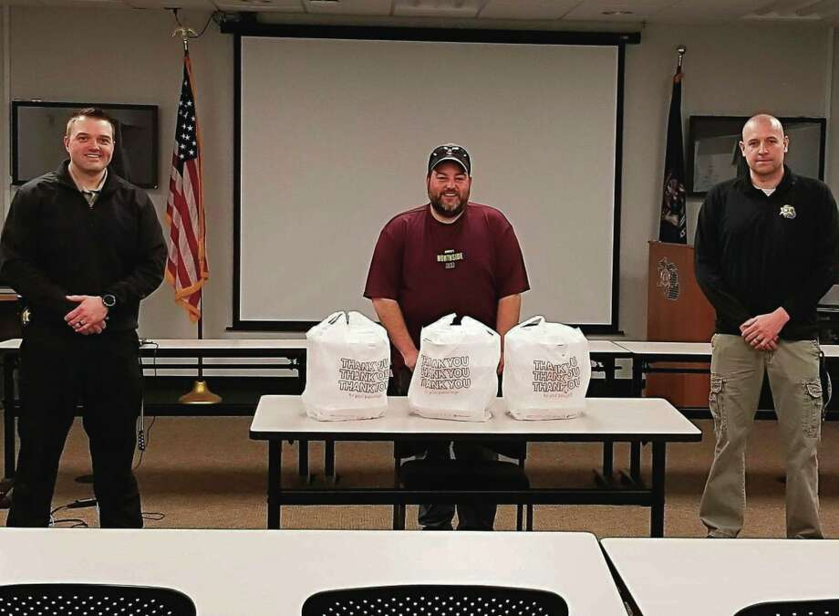 """Josh Sagala (center), of Chopo's Northside Bar, delivered food to the Manistee County Sheriff's Office in early April asthe first delivery of the Salt City Rock & Blues """"Feed the Fight Manistee."""" The group is taking donations tothank those who are working during the coronavirus pandemic by using local restaurants to prepare food for them. (Courtesy photo)"""