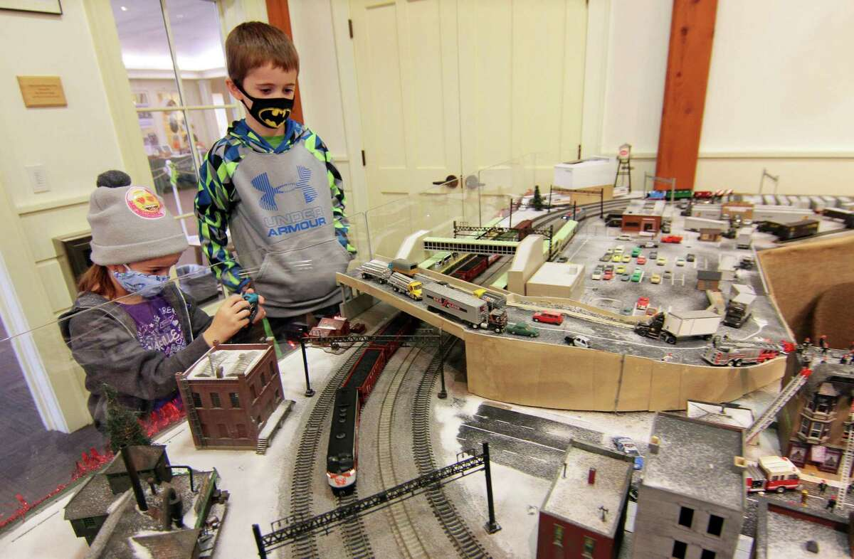 Lindsay Sherman, 8, of Norwalk, snaps pictures of the train passing by as her brother Joey, 6, watches during the Holiday Express Train Show at the Fairfield Museum and History Center in Fairfield, on Saturday Dec. 5. For more information of safety measures in place for the show and tickets visit: https://www.fairfieldhistory.org/train-show/ The trains will be on view through Sunday, Jan. 3.