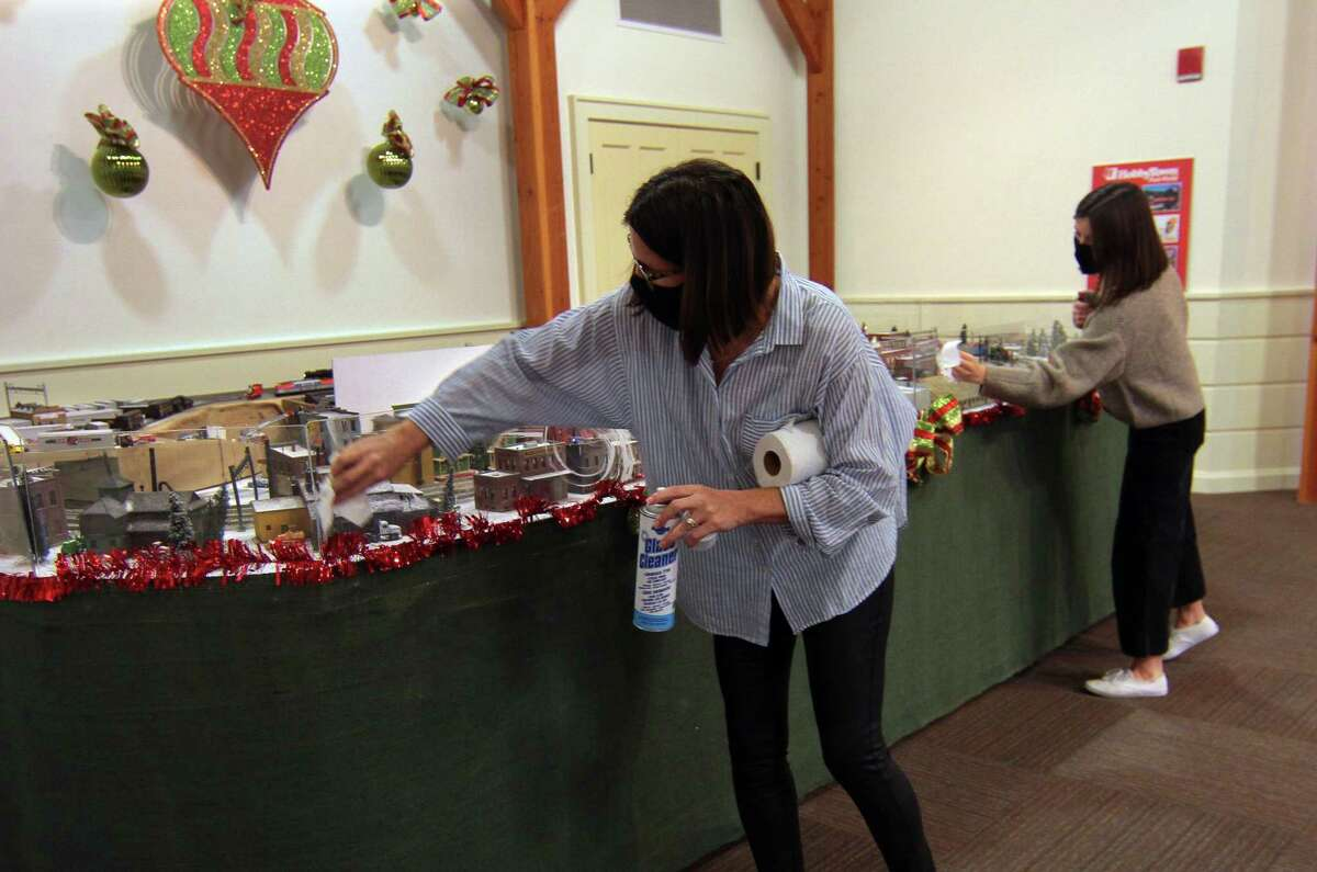 Visitor Services Manager Allison Burress and coworker Olivia Hagopian, right, disinfect the plastic dividers before another group comes in to see the Holiday Express Train Show at the Fairfield Museum.