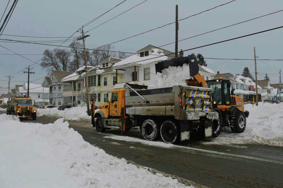 Crews work to remove snow from Edward St. on Sunday, Dec. 20, 2020, in Schenectady, N.Y. New York State Department of Transportation dump trucks were used to haul the snow away. (Paul Buckowski/Times Union)