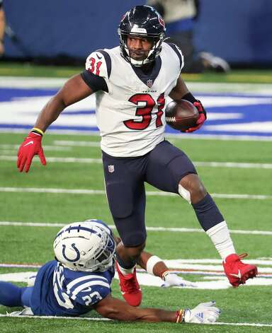 Houston Texans running back David Johnson (31) jumps out of the grasp of Indianapolis Colts cornerback Kenny Moore II (23) on a run during the fourth quarter of an NFL football game at Lucas Oil Field Sunday, Dec. 20, 2020, in Indianapolis. Photo: Brett Coomer, Staff Photographer / © 2020 Houston Chronicle