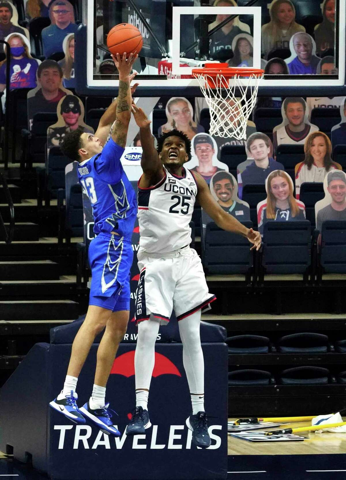 Creighton's Christian Bishop (13) shoots as UConn's Josh Carlton defends in overtime on Sunday.