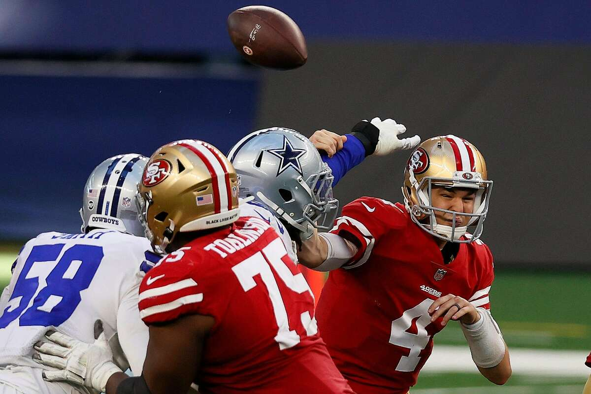 Quarterback Nick Mullens #4 of the San Francisco 49ers has the ball knocked away by the Dallas Cowboys during the fourth quarter at AT&T Stadium on December 20, 2020 in Arlington, Texas.