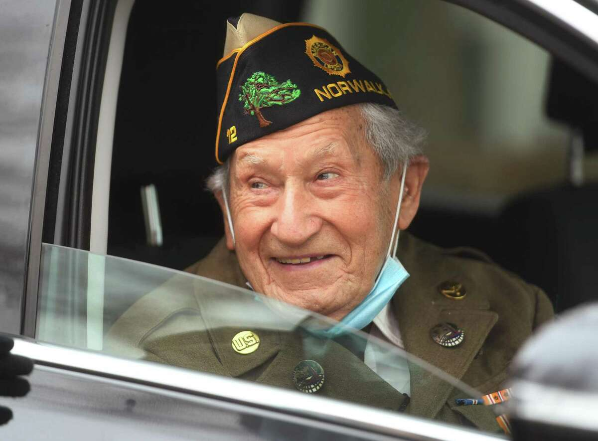 Wearing his World War 2 uniform, veteran Nick Samodel celebrates his 100th birthday with a drive-by birthday parade outside his home on Jomar Road in Norwalk on Sunday. The parade celebrating the Army Air Corps veteran began at 11 a.m., with the cars meeting in the Chick-fil-A parking lot on Connecticut Avenue, organizer Barbara Cartsounis said. She anticpated about a dozen cars would participate to celebrate the milestone birthday.