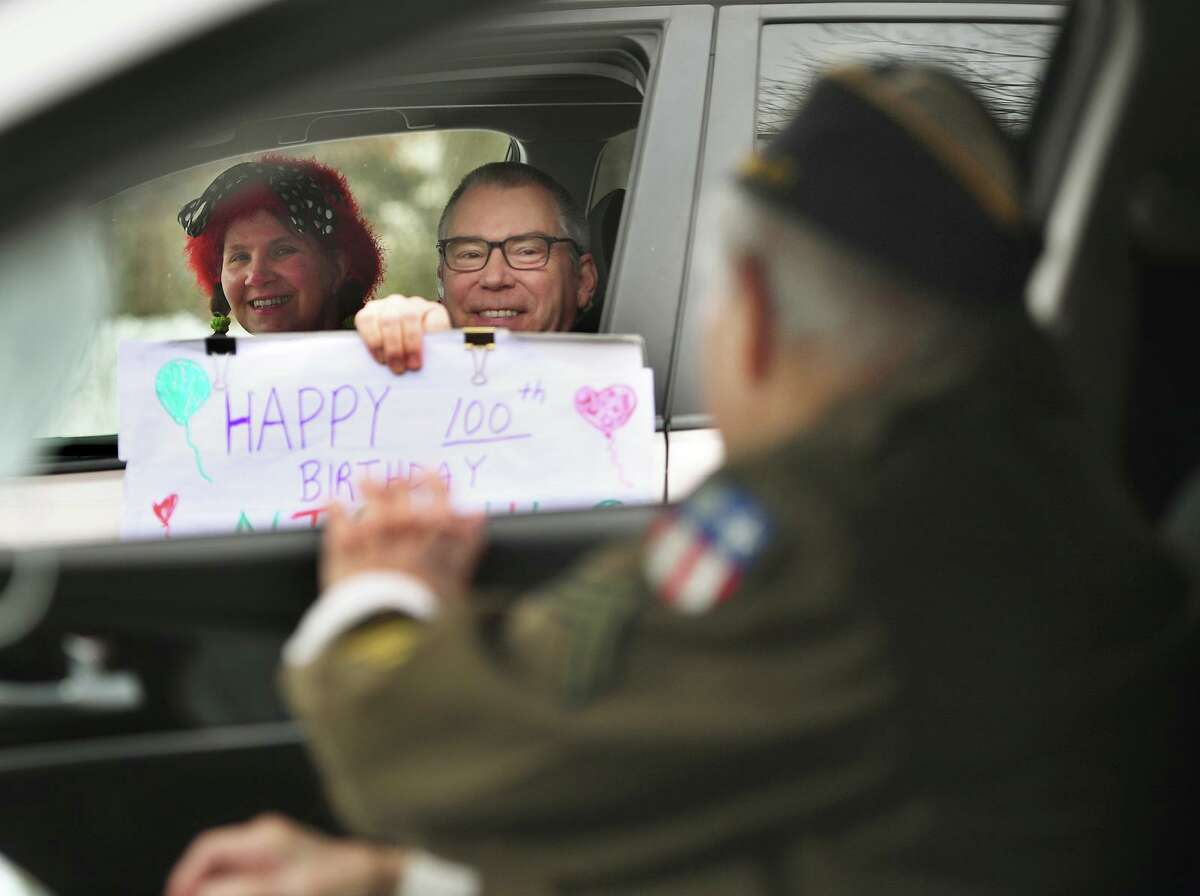 Midge Pappas and Charlie Stuttig, of Greenwich, participate in the 100th birthday drive-by parade for World War 2 veteran Nick Samodel outside his home on Jomar Road in Norwalk on Sunday. Cartsounis, a friend of Samodel, met the veteran while acting as a guardian for a trip to Washington, D.C., with her father a decade ago, she said. The trio immediately connected and while Cartsounis' father, a WWII Navy veteran, died five years ago, Samodel and Cartsounis have remained friends. Samodel lives alone in Norwalk, but has five adult children living in Connecticut, Boston, and North and South Carolina, Cartsounis said. Throughout the coronavirus pandemic, Samodel has remained cheery, Cartsounis said.