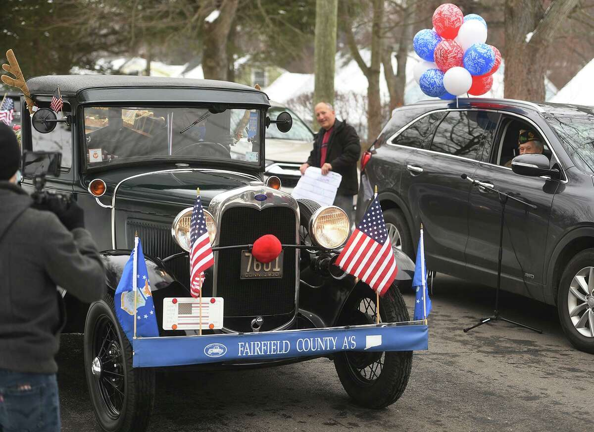 An antique car helps celebrate World War II Veteran Nick Samodel's 100th birthday on Sunday as part of a car parade.