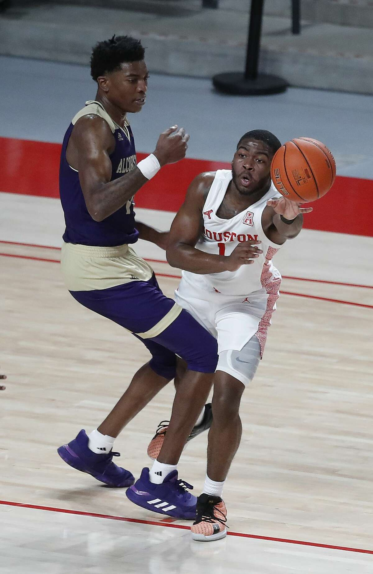 Houston Cougars guard Jamal Shead (1) passes the ball around Alcorn State Braves forward Kobe Wilson (10) during the second half of an NCAA men's basketball game at Fertitta Center Sunday, December 20, 2020, in Houston.