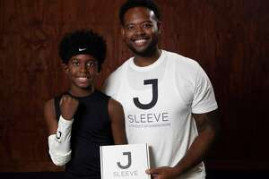 Jeremy Henderson, 37, CEO of Synergy7 and the maker of the JSleeve, and his son, Luke Henderson, 10, pose for a photograph Friday, Nov. 20, 2020, at former NBA player Brian Skinner's Texas Outlaws Basketball Gym in Fulshear. Jsleeve is a sensor-filled sleeve that basketball players wear to help with shooting form.
