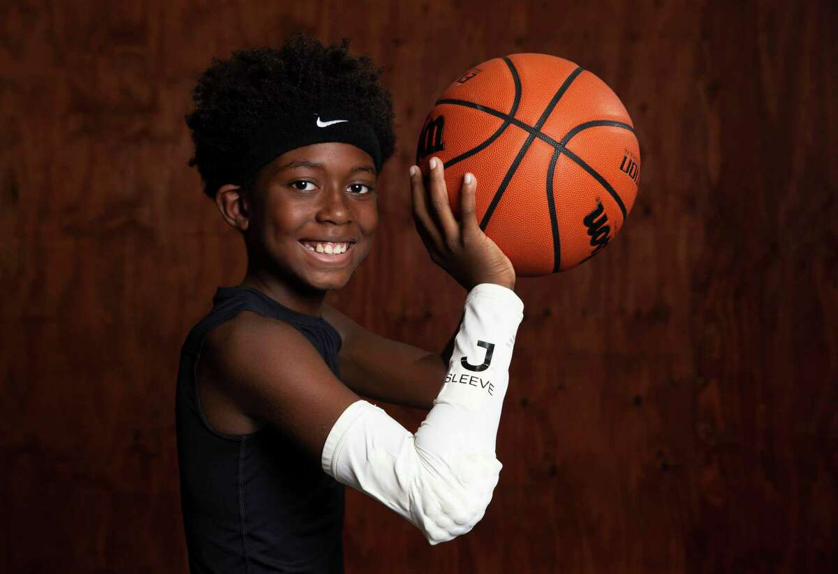 Luke Henderson, 10, pose for a photograph with the JSleeve, which is produced by his father, Jeremy Henderson, 37, CEO of Synergy7, Friday, Nov. 20, 2020, at former NBA player Brian Skinner's Texas Outlaws Basketball Gym in Fulshear. Jsleeve is a sensor-filled sleeve that basketball players wear to help with shooting form.