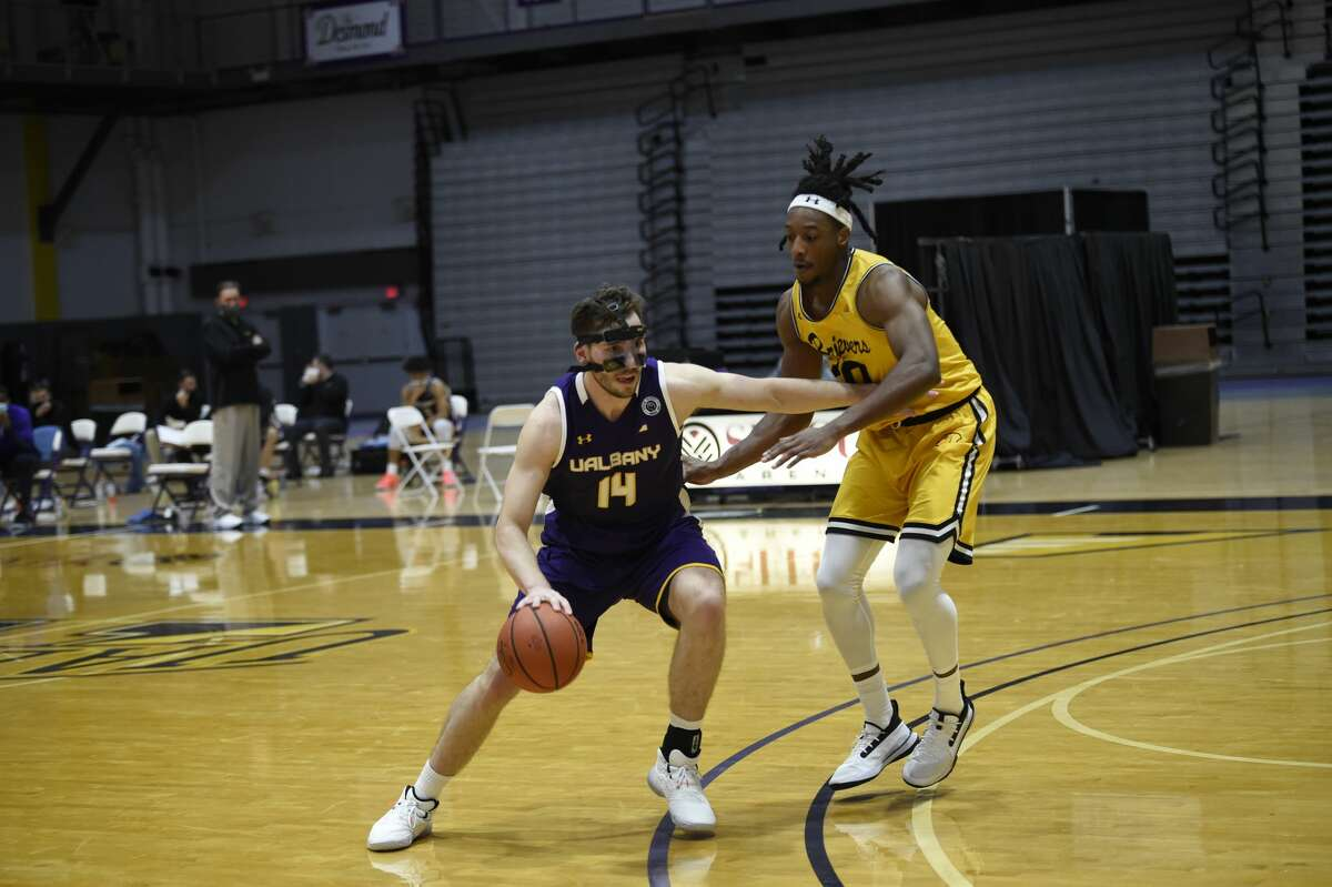 UAlbany junior forward Adam Lulka (14) looks to drive on UMBC's Daniel Akin in an America East Conference basketball game Sunday, Dec. 20, 2020, at SEFCU Arena. (Kathleen Helman / UAlbany athletics)